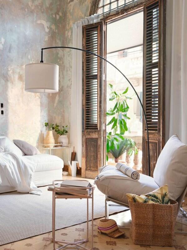 Wohnzimmer mit weißen Polstermöbeln, einer großen Stehlampe und geöffneten Türen