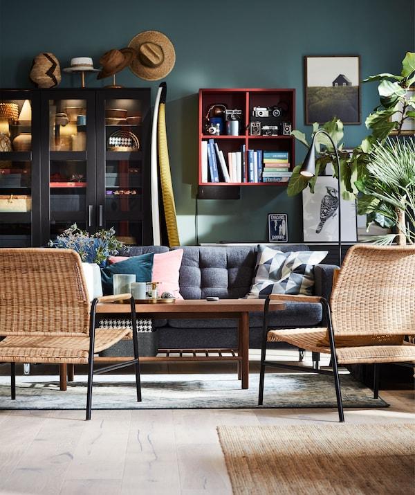 Wohnzimmer, u. a. mit zwei ULRIKSBERG Sesseln aus Rattan rund um einen Couchtisch. Im Hintergrund sind Regale zu sehen.