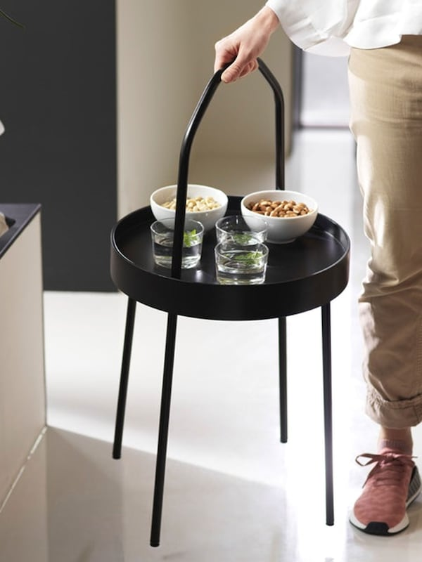 Woman carrying BURVIK black side table with snacks and drinks
