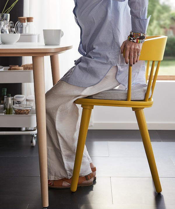Woman in a semi-seated position using her hands to gain support from the sturdy back of a yellow OMTÄNKSAM chair.