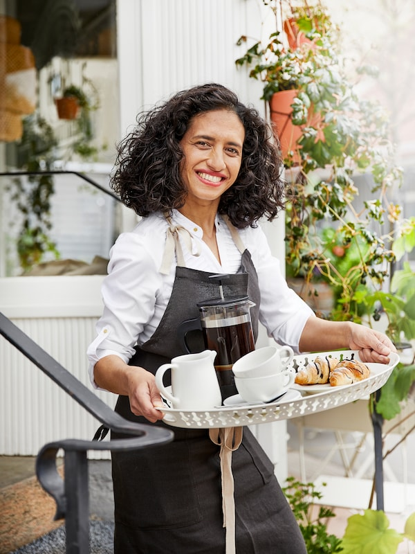 Woman in an apron carrying a tray with cakes, cups, a jug and a coffee dispenser in front of greenery outside.