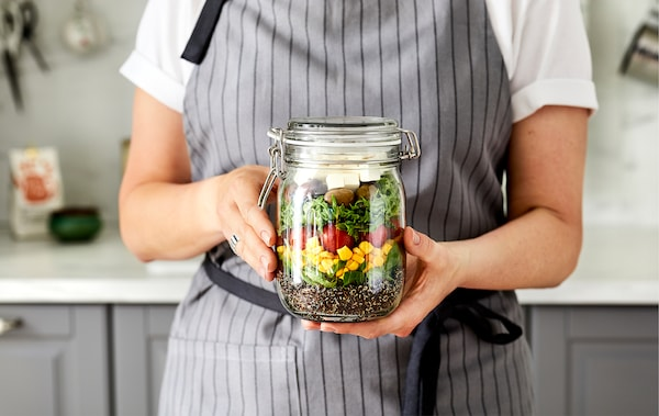 Woman in apron standing in kitchen, a loose two-hand grip holding up a tall glass jar filled with a layered, colourful salad.