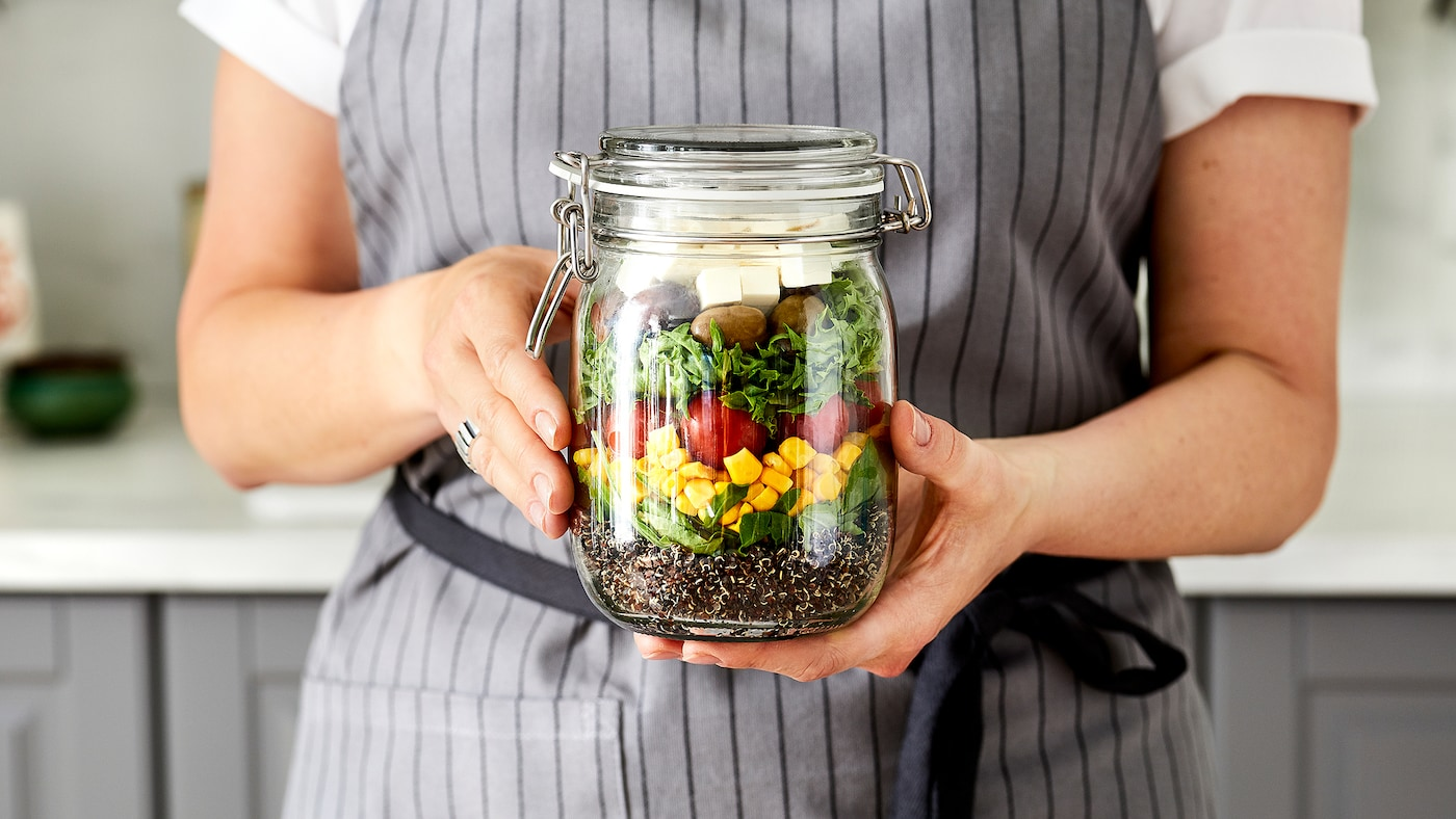 Woman in apron standing in kitchen, a loose two-hand grip holding up a glass jar filled with a layered, colourful salad.