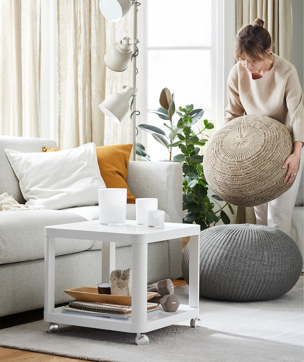 Woman lifting a pouffe in a living room with sofa, a white side table on wheels, rug and another round footstool.