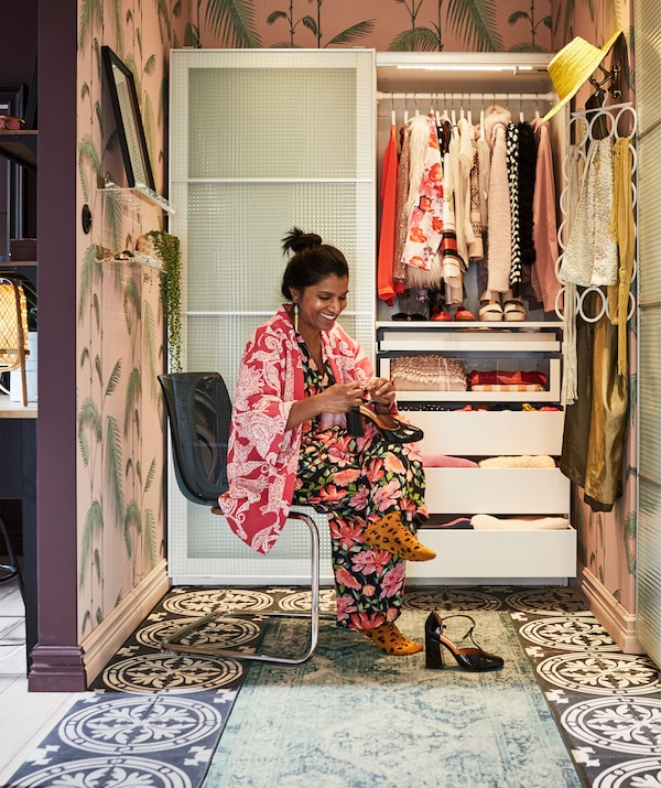 Woman on a chair in a colourful, alcove-like space fitted with a half-open, sliding-door wardrobe; accessories hung on wall.