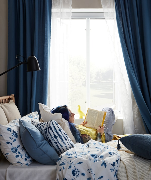 Woman reading a book, sitting on a bed with her feet on the window sill, leaning back on a mound of soft cushions.
