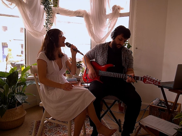 Woman singing together with a man playing guitar.