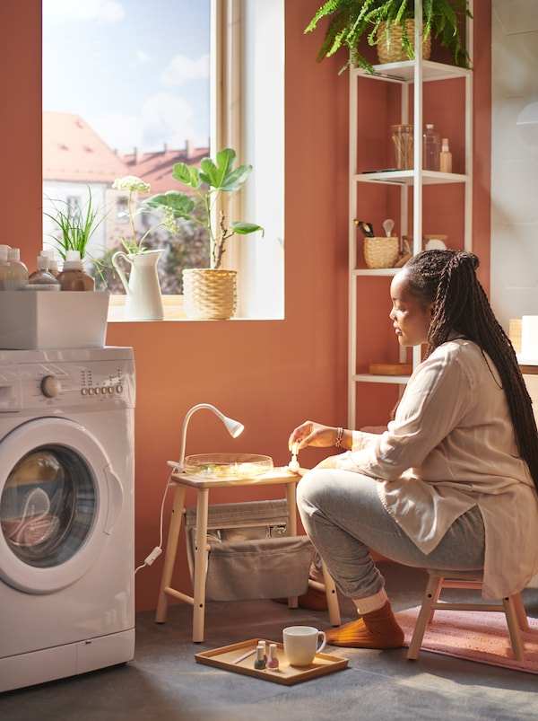 Woman sitting by a sunlit window on a VILTO step stool, with a nail-care kit on a VILTO storage stool by a washing machine.