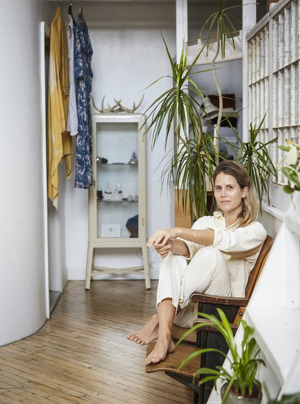 Woman sitting on a chair in a room with plants.