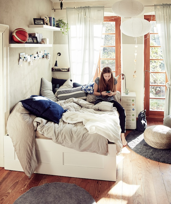 Woman sitting on a double bed with throws and cushions in a bedroom with large windows.