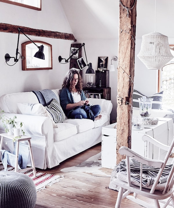 Woman sitting on a white sofa in a living room with wooden beams and floorboards.