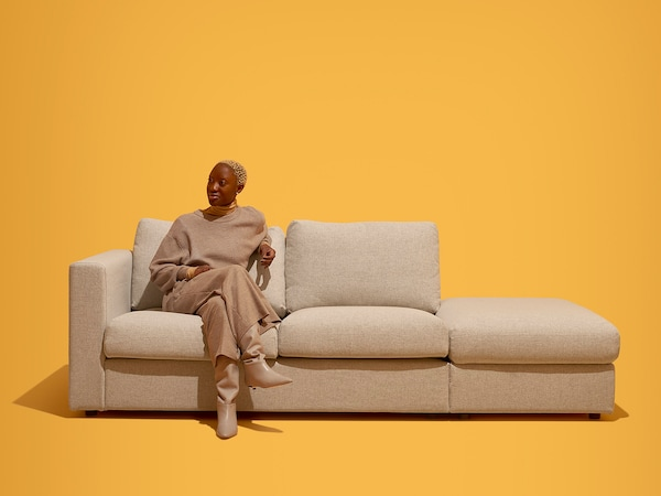 Woman sitting on edge of 2 seat sofa with ottoman on end