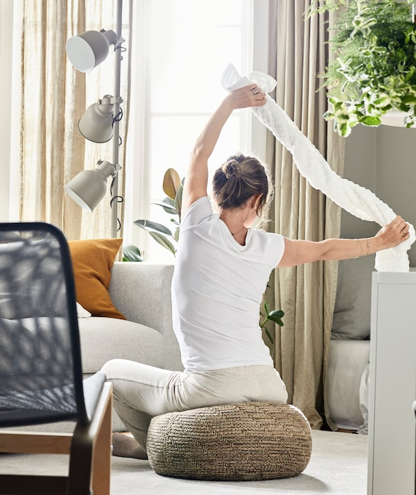 Woman sitting on pouffe in bright, neutral coloured living room stretching her shoulders using towel