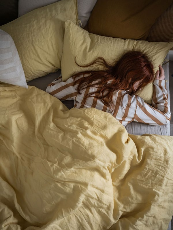 Woman sleeping on stomach in bed