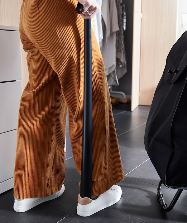 Woman standing upright in a hallway, using a light-grey OMTÄNKSAM shoehorn to put on one of her shoes.