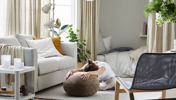 Woman stretching while sitting on SANDARED pouffe, beige