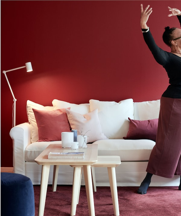 Woman striking a graceful dance pose, standing next to a sofa. White-and-red matching furniture, wall, rug and details.