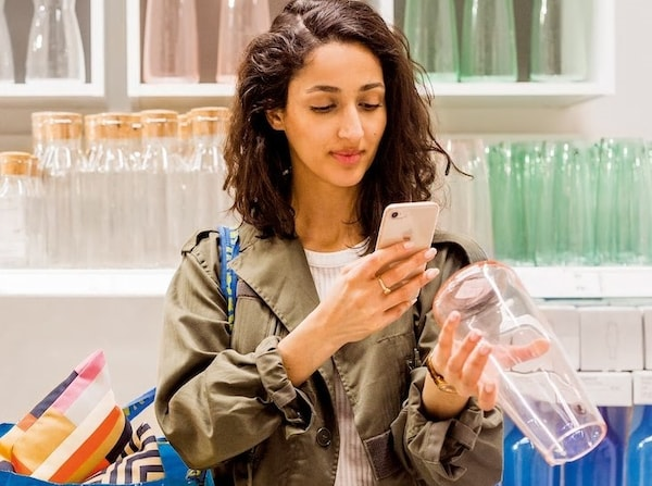 Woman using smartphone to scan a barcode on a vase
