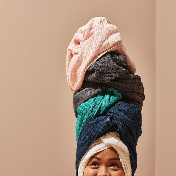 Woman's face cropped to show towels stacked on her head