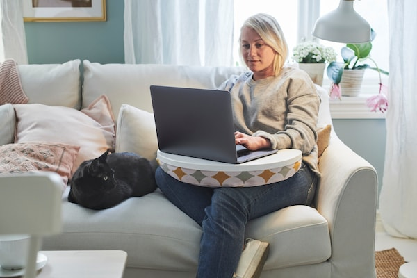 women sat on sofa with laptop and laptop tray on her lap