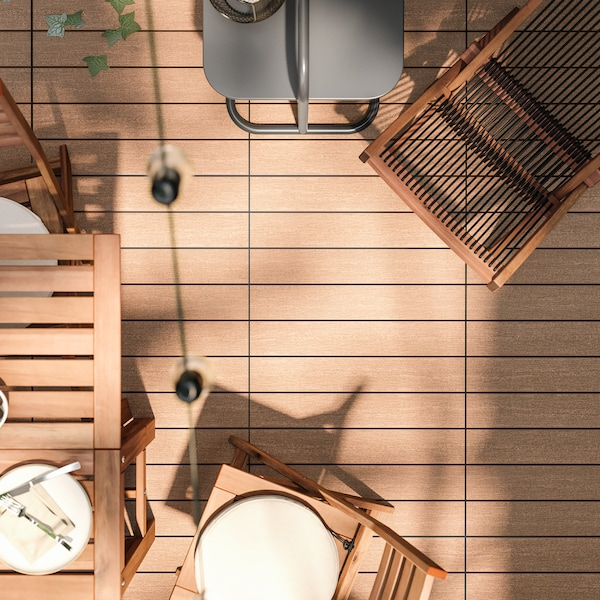 Wood-like floor decking with a wooden outdoor dining set, wooden lounger and a side table surrounding it.
