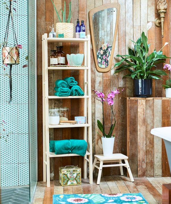 Wood spa-style bathroom with green-tiled walk-in shower, a wood shelf unit with green rolled towels and jars and plants.