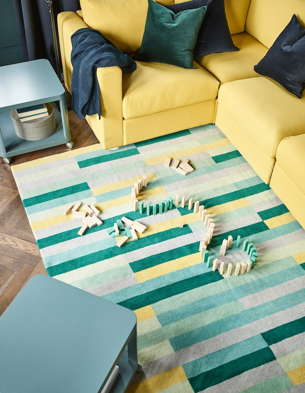 Wooden blocks on a handmade 100% wool, yellow, green, and blue mat in a fanily-friendly living room.