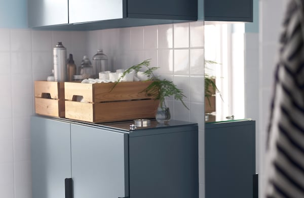 Wooden boxes on top of blue cabinets help organise bathroom essentials.