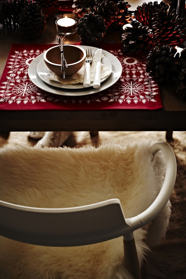 Wooden chair covered in a fluffy rug beside a festive table setting with candles.