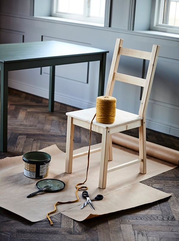 Wooden chair on cardboard with twine, a jar of paint, brush and scissors.