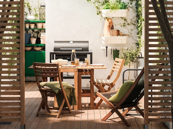 Wooden dividers offer a peek into a patio with wooden furniture, wooden decking, a black grill and green storage unit.