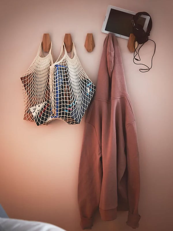 Wooden hooks on wall with mesh bag and sweater hanging
