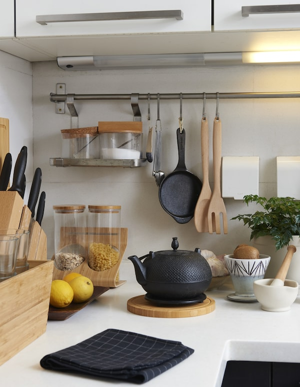 Wooden kitchen items on a white kitchen counter.