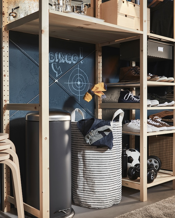 Wooden shelving unit where a large void houses a bin and a laundry bag, a cross-hairs target drawn above the latter.