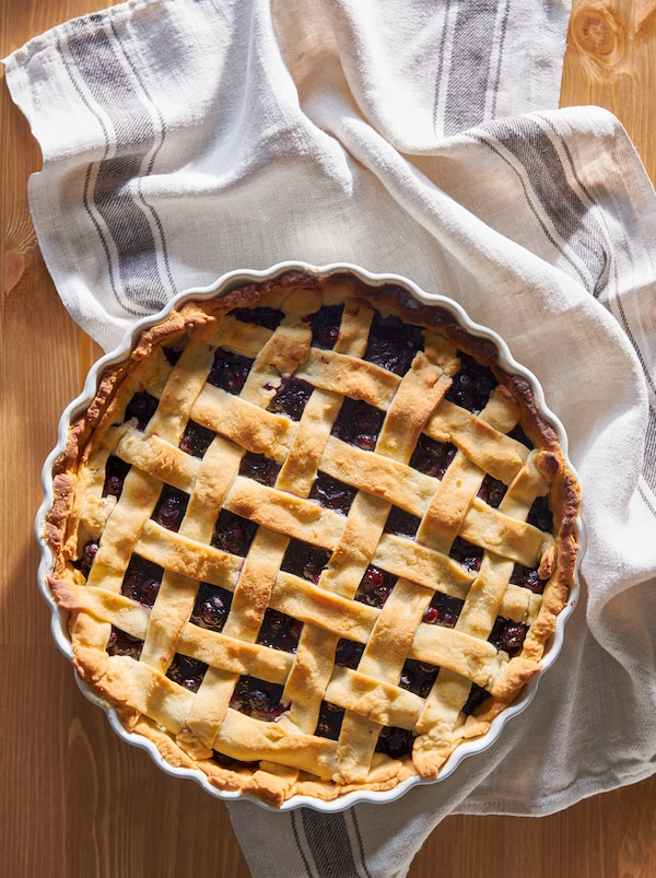 Wooden surface with a freshly baked, lattice-top blueberry pie in a VARDAGEN pie dish resting on a tea towel.