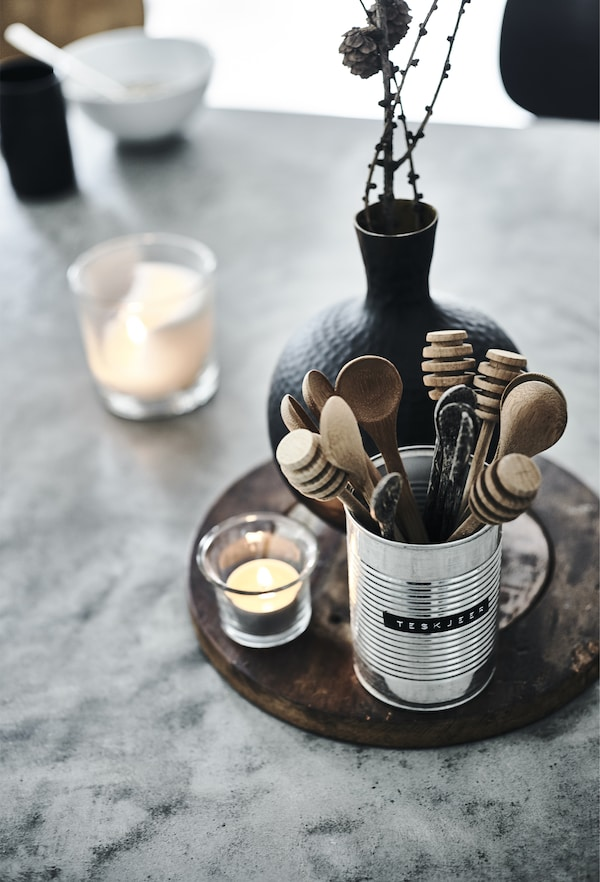 Wooden utensils in a metal can shown together with a black vase and a clear glass tealight holder with a lit tealight.