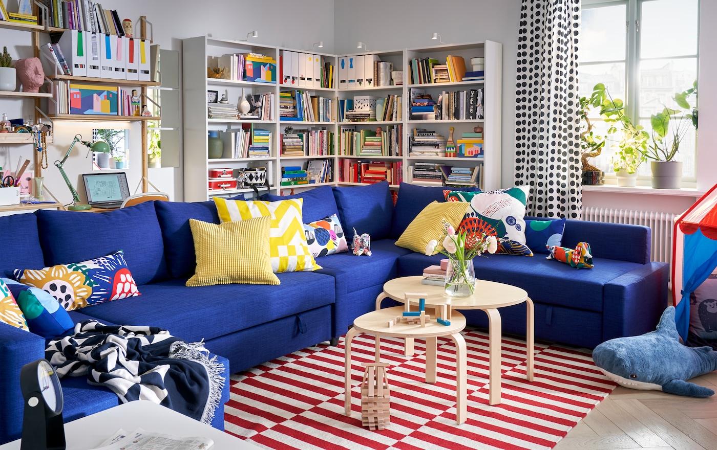 Woonkamer met FRIHETEN blauwe hoekbank met veel kussens, boekenkasten en een raam met planten in de vensterbank.