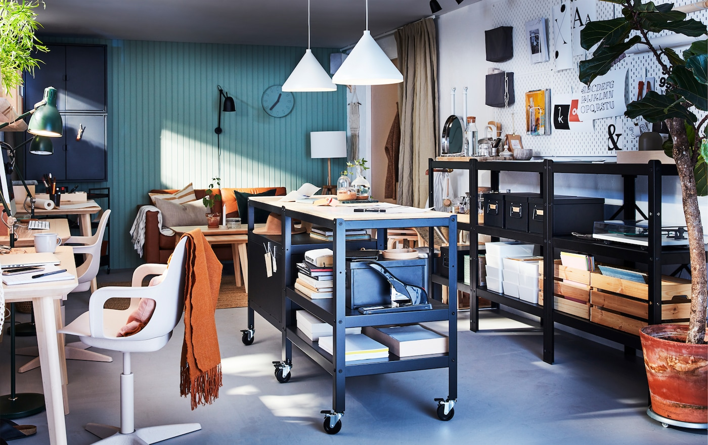 Workspace with two BROR black/wood trolleys with storage on castors, two white pendant lamps and a long black shelving unit.