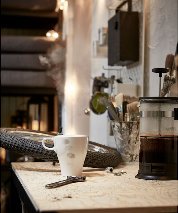Worktop in a garage-like room, a bike wheel and wrench sharing the surface with a coffee maker and a lightly stained mug.
