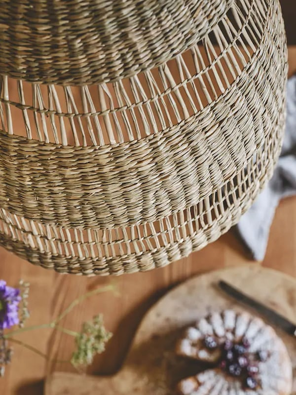 Woven seagrass pendant lamp hanging over dining table