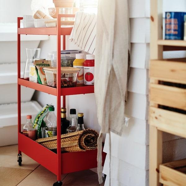 Wózek, czerwono-pomarańczowy NISSAFORS, 50.5x30x83 cm wypełniony jedzeniem.