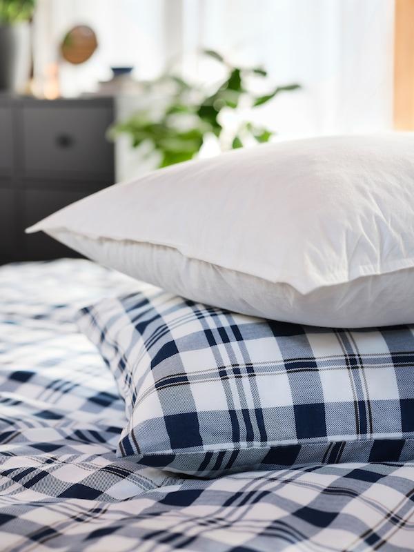 وسادة LUNDTRAV وثيرة موضوعة فوق وسادة أخرى مغطاة بكيس وسادة مربعات ولحاف مربعات.