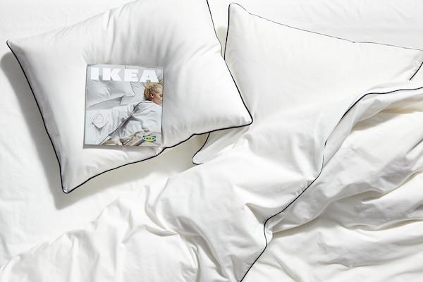وسائد بيضاء على سرير مع أغطية سرير بيضاء ، ونسخة من كتالوج ايكيا 2020 على إحدى الوسائد.