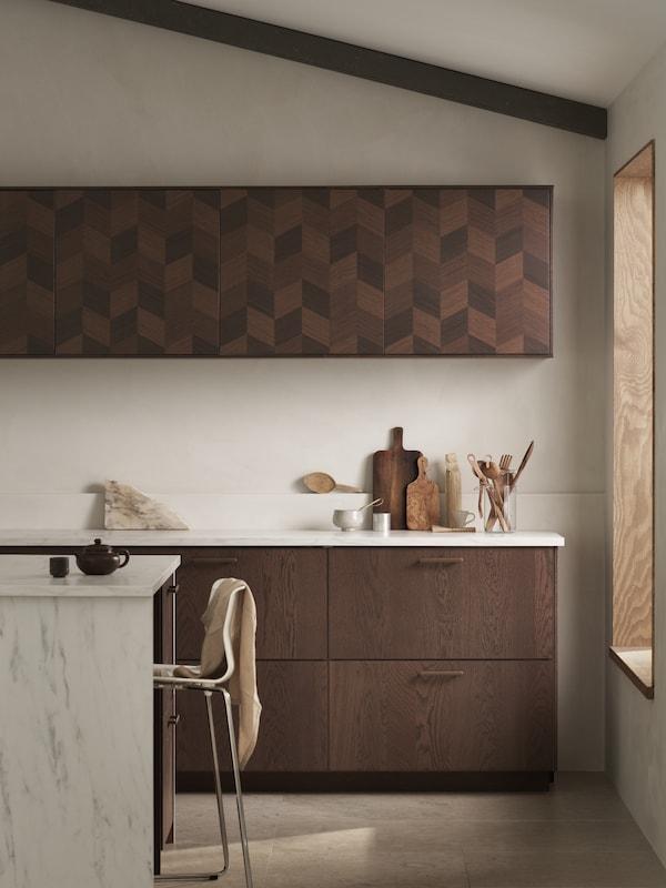 Współcześnie zaprojektowana kuchnia z szufladami SINARP i uchwytami NYDALA, drzwiami HASSLARP oraz wyspą kuchenną wykończoną imitacją marmuru.