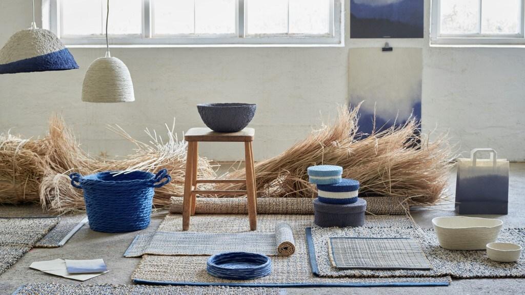 wszystkie produkty z kolekcji  FÖRÄNDRING w jednym pomieszczeniu, plecione kosze i pudełka leżące na posadzce z plecionymi dywanikami i chodniczkami.