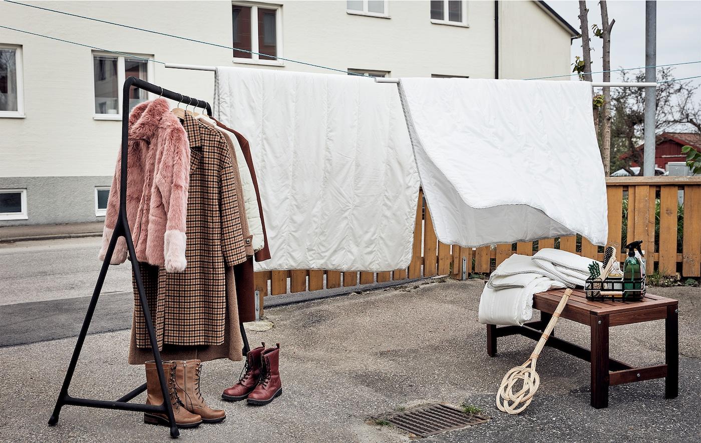 Wybrukowany ogródek przygotowany na wiosenne porządki: kołdry zawieszone na sznurkach, wieszak na ubrania, buty, tekstylia, akcesoria do czyszczenia.