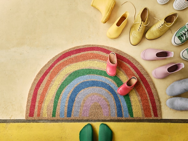Wycieraczka PILLEMARK z tęczowym wzorem leżąca na żółtej podłodze obok kolorowych butów i stóp w zielonych skarpetkach.