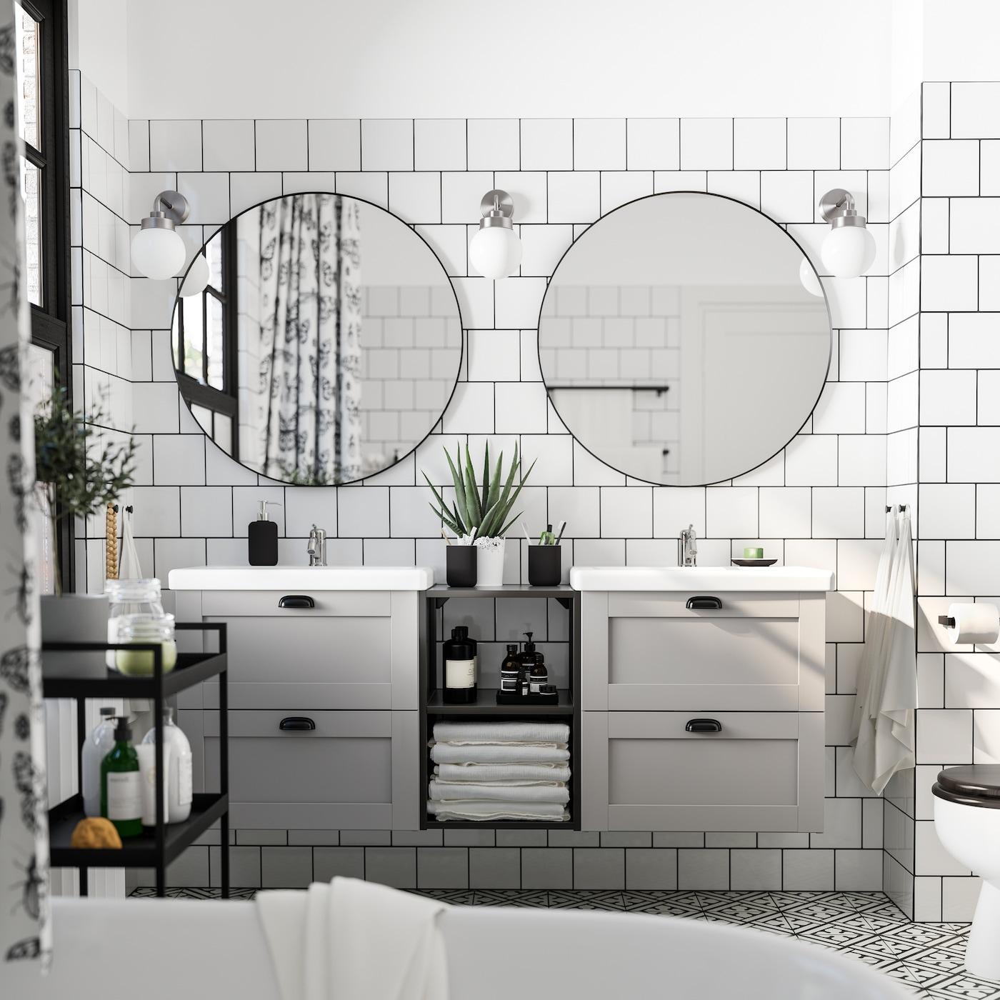 Wyłożona białymi płytkami łazienka z dwoma okrągłymi lustrami, dwoma szarymi szafkami z białymi umywalkami, czarnym wózkiem i trzema lampami ściennymi.