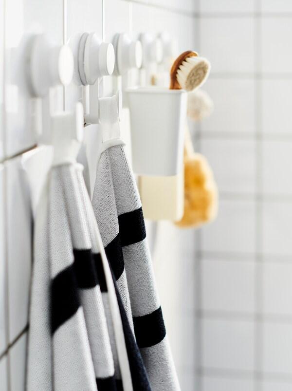 Wyłożona białymi płytkami ściana w łazience z rzędem haczyków z przyssawkami TISKEN, na których zawieszono ręczniki, szczotkę i inne akcesoria łazienkowe.
