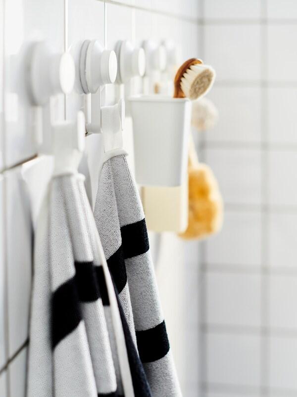 Wyłożona płytkami ściana w łazience z rzędem haczyków z przyssawkami TISKEN, na których zawieszono ręczniki, szczotkę i inne akcesoria łazienkowe.
